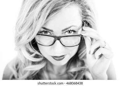 Portrait of young slim woman smiling in studio in black and white with glasses looking through