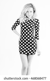 Portrait of young slim woman smiling in studio in black and white in dotted dress