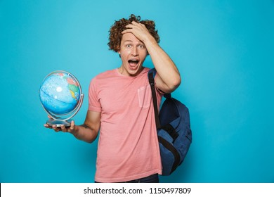 Portrait of young smarty guy with curly hair wearing backpack holding globe at geography lesson isolated over blue background
