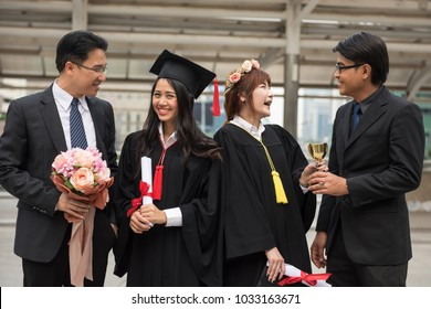 Portrait of Young smile female students in black graduation gowns happy with fathers. Portrait with delight and graceful feeling. Commencement day. Successful education concept.
