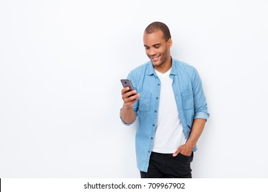 Portrait of young smiling african male student, typing sms on his phone, wearing casual jeans outfit, hand in the pocket, on pure white background