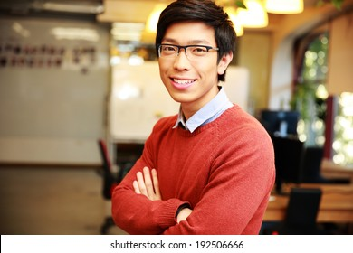 Portrait of a young smiling asian man with arms folded standing in office