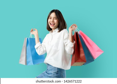 Portrait of young smiling asian woman casual clothes holding multicolored shopping bags on light blue background.