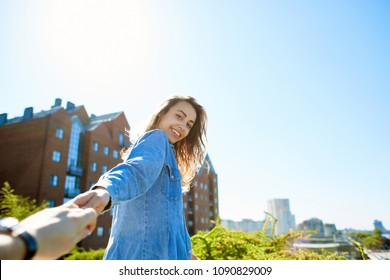 portrait of a young smiling attractive woman in jeans clothes at sunny day on the blue sky background. happy woman gives a hand to someone like follow me . first person view.