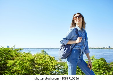 portrait of a young smiling attractive woman in jeans clothes at sunny day on the blue sky and river background. joyful woman posing in city scape.