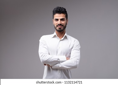 Portrait of young smiling bearded man wearing white shirt standing with arms crossed