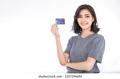 Portrait of young smiling beautiful Asian woman presenting credit card in hand showing trust and confidence making payment, online shopping telemarketing e-commerce concept with copy space