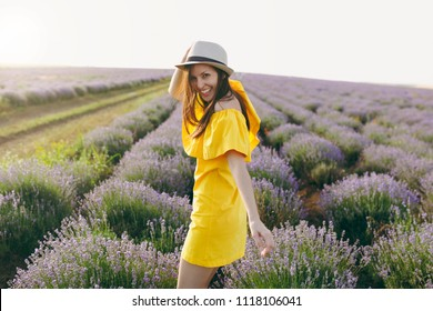 Portrait of young smiling beautiful woman in yellow dress, hat on purple lavender flower blossom meadow field outdoors on summer nature background. Happy female near flowering bush. Lifestyle concept