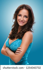 Portrait of young smiling beautiful woman with dark hair in blue dress on blue background.