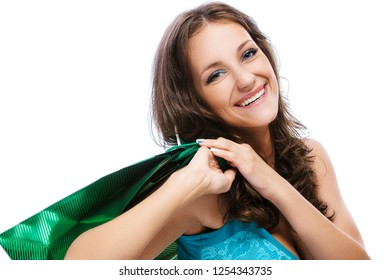 Portrait of a young smiling beautiful woman with dark hair in blue dress with green bag, isolated on white background.