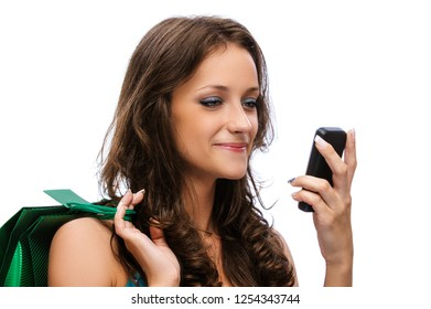 Portrait of a young smiling beautiful woman with dark hair in blue dress with green bag and phone, isolated on white background.