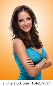 Portrait of young smiling beautiful woman with dark hair in blue dress on orange background.