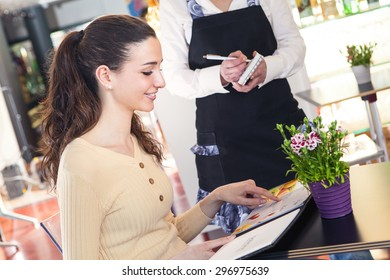 Portrait of young and smiling beautiful woman ordering to a waitress in a restaurant
