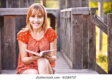 Portrait of young smiling beautiful woman wearing red dress and holding book sitting at summer green park.