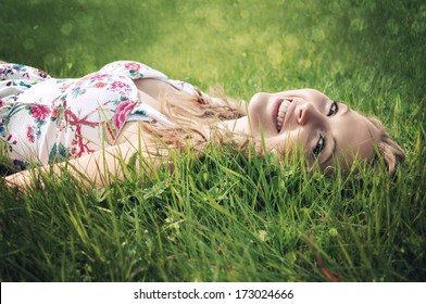 Portrait of a young smiling blonde woman lying on green grass.