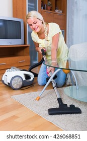 Portrait of young smiling blonde woman vacuuming in living room at home