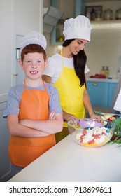 Portrait of young smiling boy in cook form who standing in the kitchen, near his mother who cooking food
