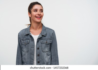 Portrait of young smiling brunette lady wears in white t-shirt and denim jackets, looks away with happy expression, stands over white background with copy space on the right side.
