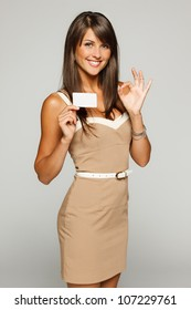 Portrait of young smiling business woman holding credit card and showing OK sign