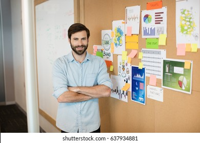 Portrait of young smiling businessman with arms crossed standing by charts on soft board at office
