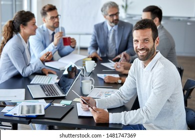 A portrait of a young smiling businessman  a meeting and presentation in the office. Business concept