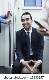 Portrait of young smiling businessman sitting on the subway