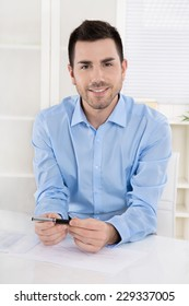 Portrait of a young smiling businessman sitting in his office wearing blue shirt.