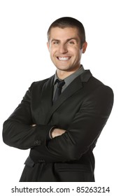 Portrait of young smiling businessman standing with folded hands isolated on white background