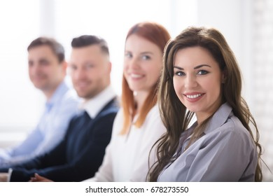 Portrait Of Young Smiling Businesswoman With Her Colleagues In Office