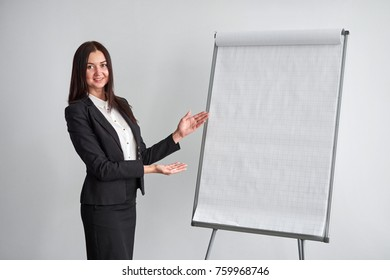 Portrait of young smiling businesswoman standing by flipchart in office
