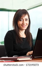 Portrait of a young smiling businesswoman using her computer