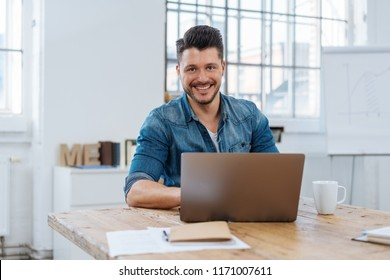 Portrait of young smiling cheerful man working in front of laptop