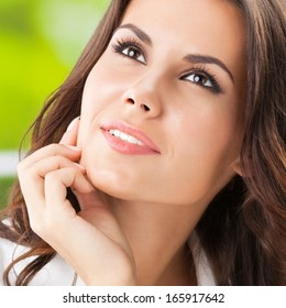 Portrait of young smiling cheerful thinking business woman at office