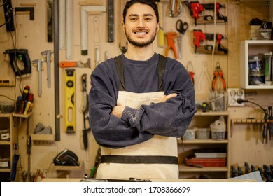 portrait of young smiling confident carpenter at work place, handsome caucasian craftman love cutting wood, work in factory