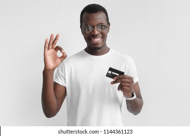 Portrait of young smiling dark skin african american man in white t shirt holding credit card and showing okay sign isolated on gray background