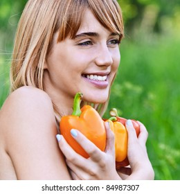 Portrait of young smiling fair-haired woman holding several vegetables and looking somewhere at summer green park.