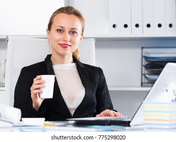 Portrait of young smiling girl with cup of water in the office