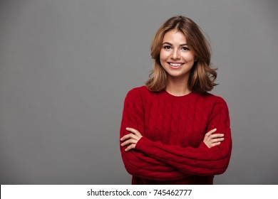 Portrait of a young smiling girl in red sweater standing with arms folded and looking at camera isolated over gray background