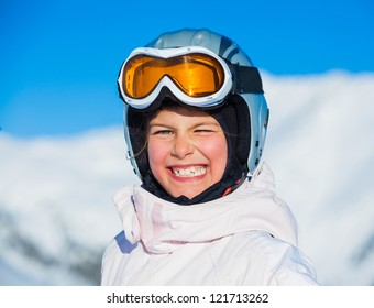 Portrait of young smiling girl a ski outfit at winter outdoor in the Zillertal Arena, Austria