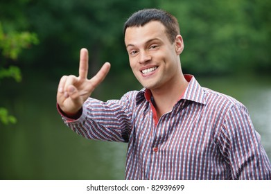 """Portrait of young smiling handsome man showing """"peace"""" sign, wearing chequered shirt, standing at summer green park."""