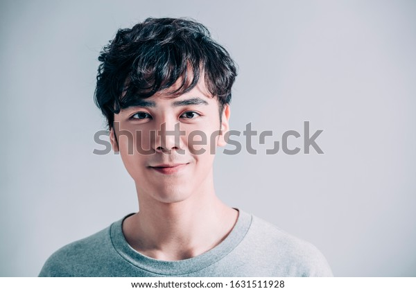portrait of young smiling handsome man isolated on gray background