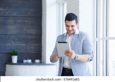 Portrait of young smiling Indian businessman with laptop sitting in modern office.