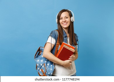 Portrait of young smiling lovely woman student in denim clothes with backpack headphones listening music, holding school books isolated on blue background. Education in high school university college