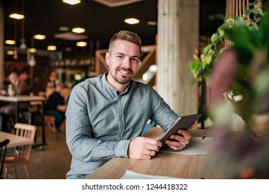 Portrait of a young smiling man with a digital tablet in a modern cafe.