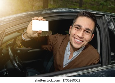 Portrait of young smiling man inside his new car posted outside the window showing the driver license or other document, free space for text in the card.
