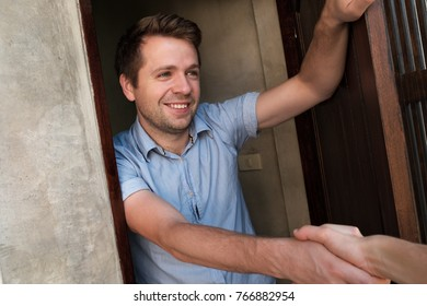Portrait of young smiling man opening the door to his friend and welcoming him shaking hand. Invite somebody for party.