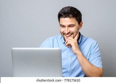 Portrait of young smiling man sitting at the desk with laptop computer over gray background