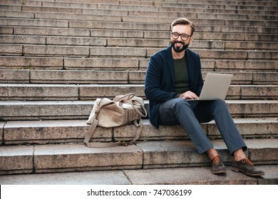 Portrait of young smiling man using laptop computer while sitting on stairs outdoors