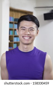 Portrait of young smiling man in a yoga studio