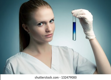 Portrait of a young smiling medical doctor woman (student) holding a test tube filled with blue liquid dissolving in crystal liquid, and posing over blue background. Studio shot